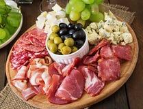 Antipasto som sköter om uppläggningsfatet med bacon, knyckigt, salami, ost och druvor Royaltyfri Bild