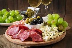 Antipasto som sköter om uppläggningsfatet med bacon, knyckigt, salami, ost och druvor Fotografering för Bildbyråer