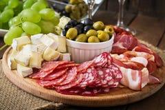 Antipasto som sköter om uppläggningsfatet med bacon, knyckigt, salami, ost och druvor Royaltyfria Foton
