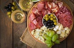 Antipasto som sköter om uppläggningsfatet med bacon, knyckigt, salami, ost och druvor Arkivfoton