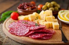 Antipasto som sköter om uppläggningsfatet med salami och ost Royaltyfri Fotografi