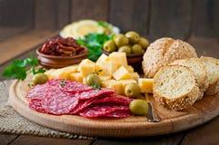 Antipasto som sköter om uppläggningsfatet med salami och ost Arkivfoto