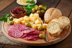 Antipasto som sköter om uppläggningsfatet med salami och ost Arkivfoton