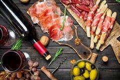 Antipasto tło Różnorodna mięsna zakąska z oliwkami, jamon i czerwonym winem, obraz stock