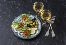 Antipasto y vino mediterráneos del estilo Salmón ahumado, aguacate, bruschetta del arugula, aceitunas y dos vidrios de vino blanc Foto de archivo