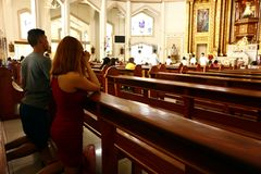 Catholic devotees kneel and pray inside the Antipolo Cathedral. ANTIPOLO CITY, PHILIPPINES – JULY 3, 2019: Catholic devotees kneel and pray inside the royalty free stock images