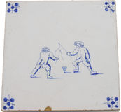 Antiqe tile of two boys spinning top Royalty Free Stock Photo