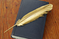 Antiquarian book. Gold quill pen and antiquarian book on grunge wood board Royalty Free Stock Image