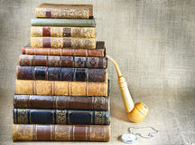 Antiquarian books, tobacco pipe and the clock Stock Photos