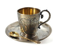 Antiquarian cup. The antiquarian silver cup with a saucer and a spoon is on a Stock Photos
