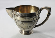 Antiquarian milk jug. Antiquarian silver milk jug with gold Stock Image