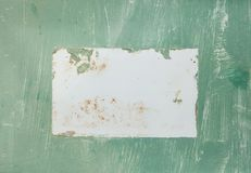 An antique aged sign with green textured paint and a white rectangle blank area in the middle. royalty free stock images