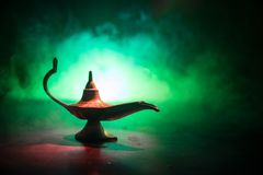 Antique Aladdin arabian nights genie style oil lamp with soft light white smoke, Dark background. Lamp of wishes concept. Selective focus royalty free stock image