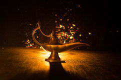 Antique Aladdin arabian nights genie style oil lamp with soft light white smoke, Dark background. Lamp of wishes concept. Toned Royalty Free Stock Photo