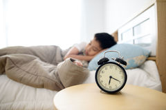 Antique alarm clock in the bedroom. Selective focus on the antique alarm clock beside the bed and young sleeping boy Royalty Free Stock Image