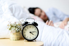Antique alarm clock and the girl. Selective focus on antique black alam clock in front of young and beautiful asian girl on the bed Stock Image