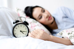 Antique alarm clock and the girl. Selective focus on antique black alam clock in front of young and beautiful asian girl on the bed Stock Photo