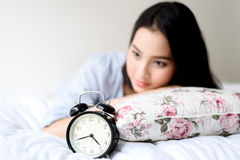 Antique alarm clock and the girl. Selective focus on antique black alam clock in front of young and beautiful asian girl on the bed Stock Images