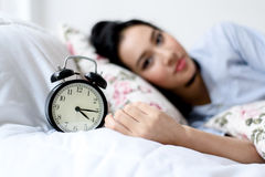 Antique alarm clock and the girl. Selective focus on antique black alam clock in front of young and beautiful asian girl on the bed Stock Photography