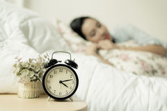 Antique alarm clock and the girl. Vintage color tone. Selective focus on antique black alam clock in front of young and beautiful asian girl on the bed Stock Image