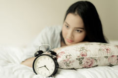 Antique alarm clock and the girl. Vintage color tone. Selective focus on antique black alam clock in front of young and beautiful asian girl on the bed Royalty Free Stock Photos