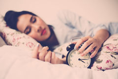 Antique alarm clock and the girl. Vintage color tone. Selective focus on antique black alam clock in front of young and beautiful asian girl on the bed Stock Images