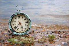 Alarm clock in the water. Antique alarm clock on a lakeshore in pebble covered sand Royalty Free Stock Images