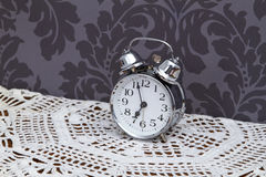 Antique alarm clock on table cloth Royalty Free Stock Images