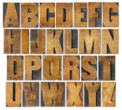 Antique alphabet set in wood type. Complete English alphabet - collage of 26 isolated vintage wood letterpress printing blocks, scratched and stained by ink Stock Photography