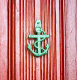 Antique anchor shaped knokcer on a red vintage door Royalty Free Stock Photography
