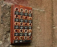 Antique apartment buzzer still in use. Rusted apartment buzzer at an apartment entrance stock photo