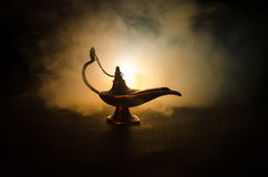 Antique arabian nights style oil lamp with soft light white smoke, Dark background. Lamp of wishes concept. Toned Stock Photography