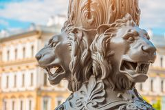 Antique architecture out of focus, in the foreground the sculpture of lions on a pillar, Saint-Petersburg, Russia. Stock Photos