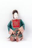 Antique Asian doll. Closeup of antique Asian doll in traditional clothing, isolated on white background stock photo