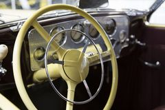 Antique Automobile Chrome Dashboard, Yellow Steering Wheel, Red Leather Seats, Out of Focus Autos in Background. View Antique Automobile Chrome Dashboard, Yellow stock image