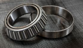 Automotive tapered roller bearing and race on carbon fiber cloth. Antique automotive tapered roller bearing and race on plain weave carbon fiber cloth Royalty Free Stock Photos
