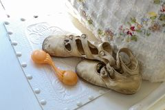Antique baby shoes and rattle by floral and fringed pillow royalty free stock photography