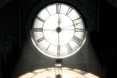 Antique Backlit Clock And Empty Chair. A 3D render of the attic room behind an antique tower clock brightly illuminated by the sun revealing an empty chair Stock Photo
