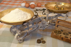 Antique balance with weights. Antique balance or scales with brass weights and flour in a cosy home Stock Photos