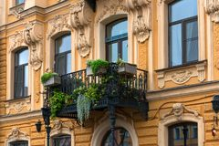 Antique balcony with plants at historical building. RUSSIA, SAINT PETERSBURG - AUGUST 18, 2017:  antique balcony with plants at historical building Stock Images