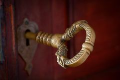 Antique beautiful bronze key in a door Stock Photo
