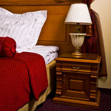 Antique bedside table and bed Royalty Free Stock Photo