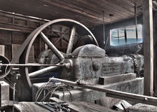 Antique Belt Driven Steam Compressor. Similar to a steam engine this antique steam driven compressor sits abandoned in the ruins of an old mine lift house. The stock photography