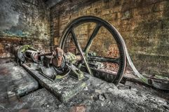 Antique belt driven steam engine in an abandoned factory royalty free stock image