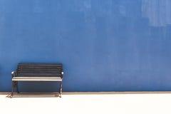 Antique bench on blue concrete wall Stock Photos