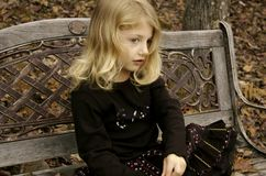 Antique Bench Girl. Cute little girl posing on a bench in autumn Royalty Free Stock Photo