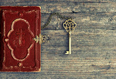 Antique bible book and golden key on wooden background Stock Photos