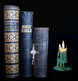 Antique Bibles beside burned down burning green candle. Three very old Bible with no copyright - one in German. Crucifix and green lit candle isolated on black stock photos