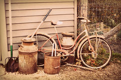 Antique Bicycle, Milk Jug and Tools. A vintage girls bicycle with a basket along the side of a house with some antique milk jugs and various gardening tools Stock Photo