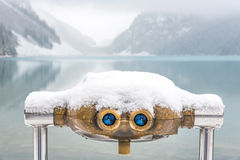 Antique binoculars in winter scenery. An antique set of binoculars covered in snow looking over blue Lake Louise and it's surrounding mountains Royalty Free Stock Photography